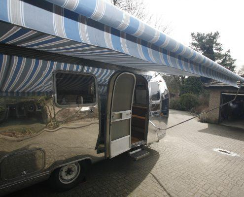Airstream caravan polished with blue stripy awning