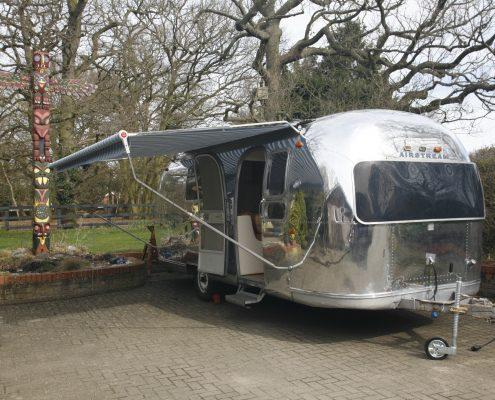Polished Airstream caravan with awning