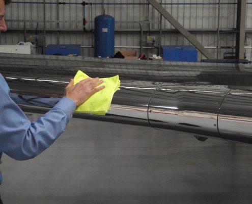 man polishing aircraft wing with cloth